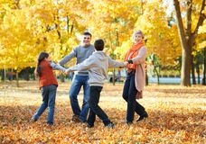 Happy family walks in autumn city park. Children and parents posing, smiling, playing and having fun. Bright yellow trees. royalty free stock photos