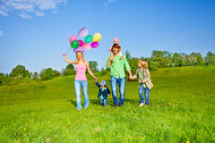 Happy family walks with balloons in park Royalty Free Stock Photo