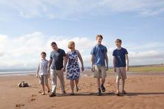 A happy family walks on the beach Stock Photography