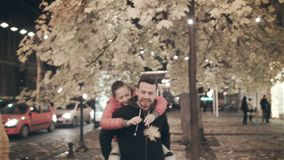 A happy family walks the evening in the city on holidays. The father carries on his back a daughter who tears a leaf. A happy family walks the evening in the stock video