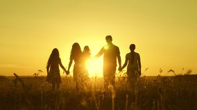 Happy family walks in field in sunset light. dad mom and daughters are walking in park in the light of sun. children and stock video footage