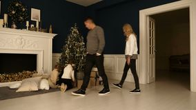 Happy family walks in living room to check the presents under the Christmas tree. stock video footage