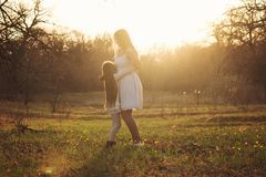 Happy family walks in the spring meadow. Family hugging outdoors in sunshine. Girl shows mother her love through sincere cuddle. Mother`s day celebration concept royalty free stock photography