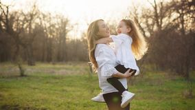 Happy family walks in the spring meadow. Mother and daughter whirl. Mother holds the child in her arms. Family time together. Joy of a spring walk. Family look stock photography