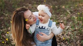 Happy family walks in the spring meadow. Family portrait close-up. Mom hugs one-year-old daughter. Baby is holding flower in her hands and is enjoying walk in stock photography