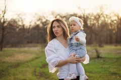 Happy family walks in the spring meadow. Young mother holds a one-year-old daughter with a worried look on face. Walk with your child in spring sunny evening royalty free stock images