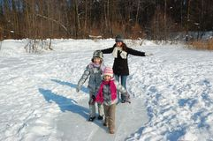 Happy family in winter, having fun and playing with snow outdoors on holiday weekend Royalty Free Stock Images