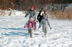 Happy family in winter, having fun and playing with snow outdoors on holiday weekend Royalty Free Stock Photography