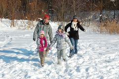 Happy family in winter, having fun and playing with snow outdoors on holiday weekend Royalty Free Stock Photos