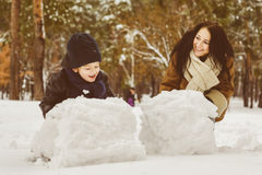 Happy family in warm clothing. Smiling mother and son making a snowman outdoor. The concept of winter activities Royalty Free Stock Photos