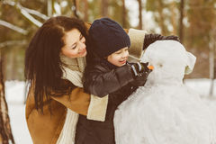 Happy family in warm clothing. Smiling mother and son making a snowman outdoor. The concept of winter activities Royalty Free Stock Photo