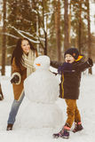 Happy family in warm clothing. Smiling mother and son making a snowman outdoor. The concept of winter activities Royalty Free Stock Image