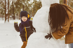 Happy family in warm clothing. Smiling mother and son play snowballs next to a snowman outdoor. The concept of winter. Activities Stock Photo