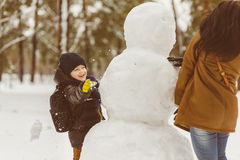 Happy family in warm clothing. Smiling mother and son play snowballs next to a snowman outdoor. The concept of winter. Activities Stock Images