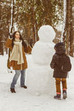 Happy family in warm clothing. Smiling mother and son play snowballs next to a snowman outdoor. The concept of winter. Activities Royalty Free Stock Photography