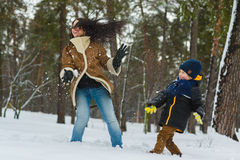 Happy family in warm clothing. Smiling mother and son play snowballs outdoor. The concept of winter activities.  Stock Photography