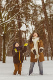 Happy family in warm clothing. Smiling mother and son playing fun game outdoor. The concept of winter activities Royalty Free Stock Image