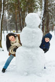 Happy family in warm clothing. Smiling mother and son standing next to a snowman outdoor. The concept of winter Royalty Free Stock Photos