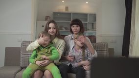 Family watching TV sitting on the couch in the guest room. Older sisters close their eyes to children because of bad stock video