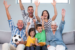Happy family watching a football match at home stock photo
