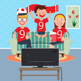 Happy Family Watching Football Together on TV Stock Photo