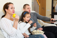 Happy family watching movie. Happy family of three watching movie in domestic interior. Focus on woman Stock Photos
