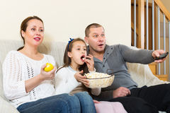 Happy family watching movie. Family of three watching movie and smiling in domestic interior. Focus on girl Stock Image
