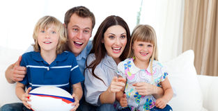 Happy family watching a rugby match. At home Stock Photography
