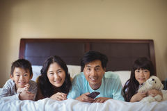 Happy family watching television in the bed room Royalty Free Stock Photo