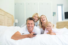 Happy family watching television in the bed room Stock Images