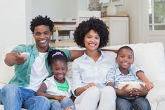 Happy family watching television eating popcorn Stock Photos