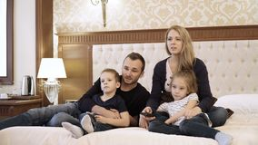 A happy family watching television in hotel room sitting on bed.  stock video footage