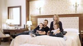 A happy family watching television in hotel room sitting on bed.  stock video