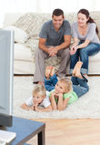 Happy family watching television together. In the living room Stock Photos