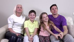 Happy family watching television together on the sofa stock video footage