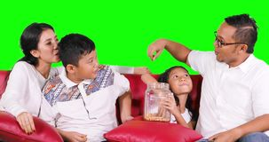 Happy family watching tv while eating snack. Happy Asian family watching tv together while eating a jar of snack and sitting on the sofa with green screen stock video