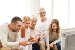 Happy family watching tv at home. Family, happiness, generation and people concept - happy family sitting on sofa and watching tv at home Stock Photography