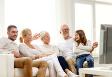 Happy family watching tv at home. Family, happiness, generation and people concept - happy family sitting on sofa and watching tv at home Royalty Free Stock Image