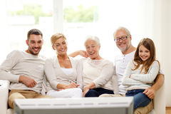 Happy family watching tv at home. Family, happiness, generation and people concept - happy family sitting on sofa and watching tv at home Stock Photo