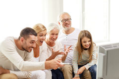 Happy family watching tv at home. Family, happiness, generation and people concept - happy family sitting on sofa and watching tv at home Royalty Free Stock Images