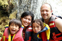 Happy family in the water. Cheerful family wearing life vest smiling at camera stock photos