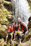 Happy family in the waterfall. Cheerful family in waterfall area wearing life vest smiling at camera stock photo