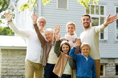 Happy family waving hands in front of house. Gesture, happiness, generation, home and people concept - happy family waving hands in front of house outdoors Stock Photography