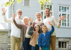 Happy family waving hands in front of house. Gesture, happiness, generation, home and people concept - happy family waving hands in front of house outdoors stock images