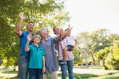 Happy family waving hands in the park Stock Images