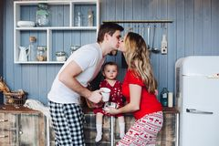 Happy family wearing Christmas pajamas cooking together with little daughter. stock photo