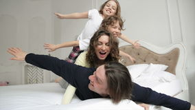 Happy Family Wearing Pajamas is Having Fun in the Bedroom. Two Playfull Children with Curly Hair and Young Couple are. Enjoying Weekend Together Lying on White stock footage