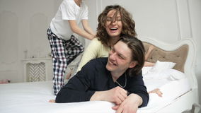 Happy Family Wearing Pajamas is Having Fun in the Bedroom. Two Smiling Adults and Joyful Boy are Playing on the White. Bed in the Morning, HD stock video