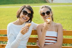 Happy family weekend, outdoor portrait of mom and daughter with ice cream in the park on a bench stock images