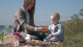 Happy family weekend, young mother is played toys with cute child boy during picnic outdoors near river at warm day stock video footage